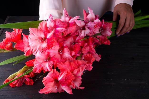 Vrouw die een mooi boeket van bloemen van roze gladiolen houdt