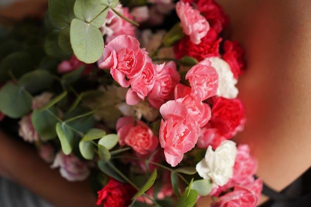 Vrouw die een mooi kleurrijk tot bloei komend bloemboeket van verse rozen van het drijfzand houdt