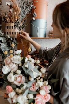 Vrouw die een mooie bloemenregeling maakt