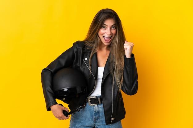 Vrouw die een motorfietshelm houdt die op geel wordt geïsoleerd die een overwinning in winnaarpositie viert