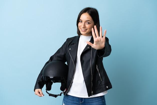 Vrouw die een motorhelm houdt die op blauw wordt geïsoleerd dat vijf met vingers telt
