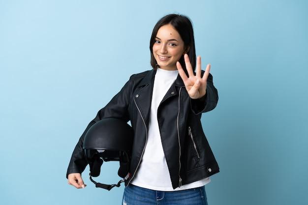 Vrouw die een motorhelm houdt die op blauwe muur gelukkig wordt geïsoleerd en vier met vingers telt