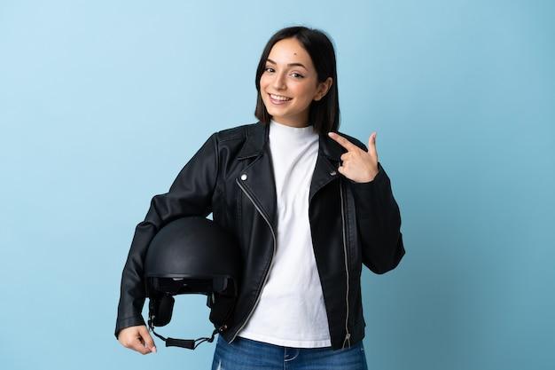 Vrouw die een motorhelm houdt die op blauwe muur wordt geïsoleerd die een duim omhoog gebaar geeft