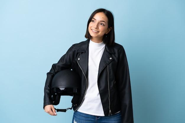 Vrouw die een motorhelm houdt die op blauwe muur wordt geïsoleerd die een idee denkt terwijl het omhoog kijken