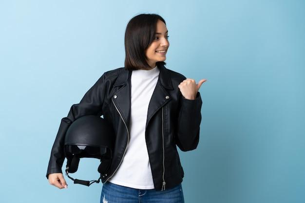 Vrouw die een motorhelm houdt die op blauwe muur wordt geïsoleerd die naar de kant wijst om een product te presenteren