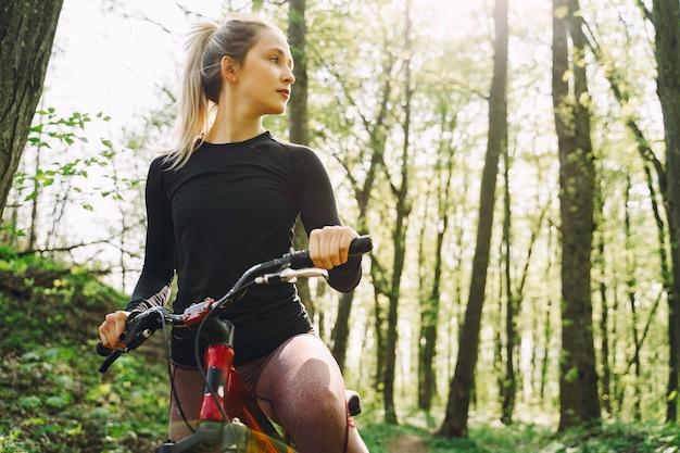 Vrouw die een mountainbike in het bos berijdt