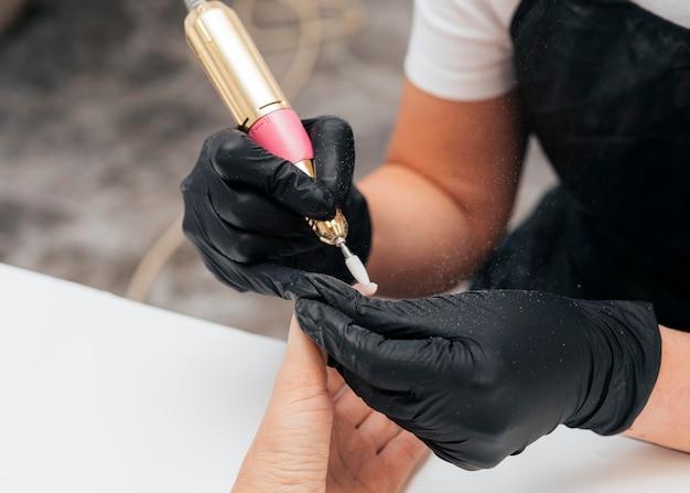 Vrouw die een nagelvijl op cliënt gebruikt en handschoenen draagt