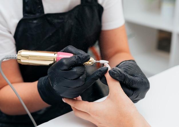 Vrouw die een nagelvijl op cliënt gebruikt