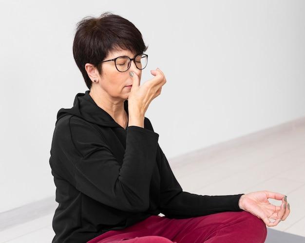 Vrouw die een neusgat bedekt tijdens het mediteren