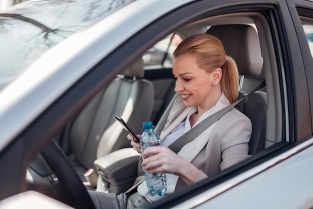 Vrouw die een onderbreking van het drijven neemt, gebruikend telefoon en drinkwater terwijl het zitten in de auto.
