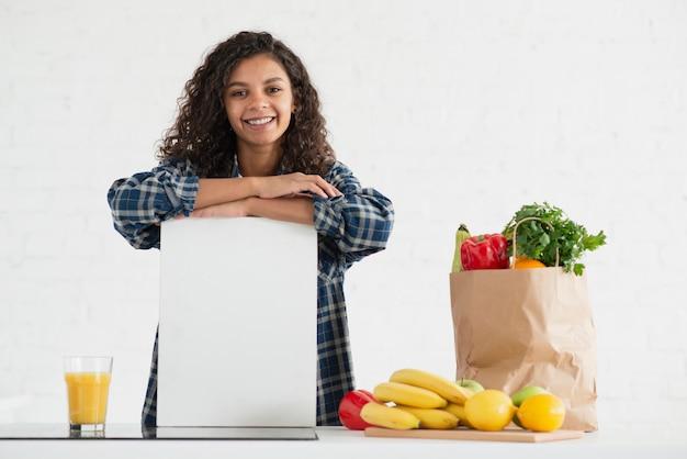 Vrouw die een onecht teken naast een plantaardige zak houdt