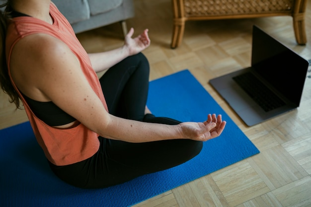 Vrouw die een online yogales volgt tijdens de quarantaine van het coronavirus