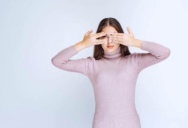 Vrouw die één oog bedekt en met een ander over haar vingers kijkt.