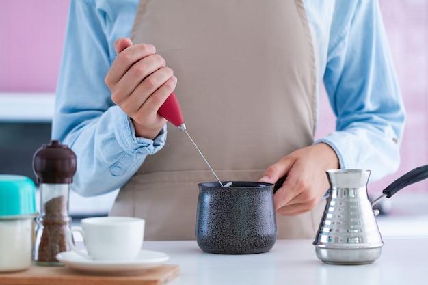 Vrouw die een opschuimer voor thuis het maken van aromatische koffie met behulp van