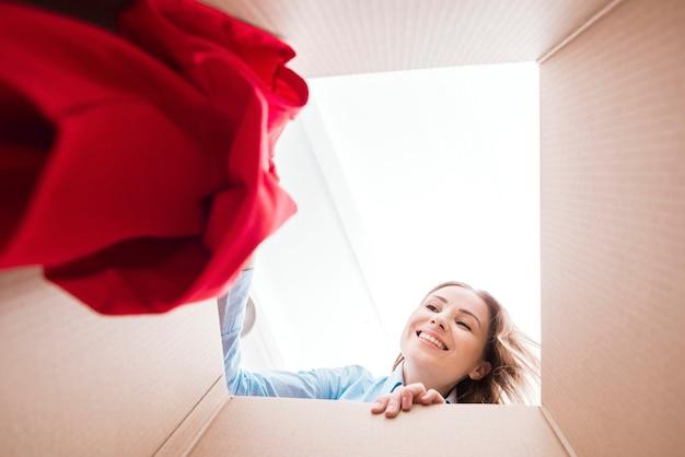Vrouw die een overhemd binnen bodem van de doosmening houdt