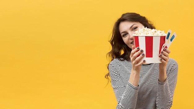 Vrouw die een paar 3d glazen en emmer met popcorn steunt