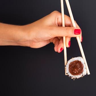 Vrouw die een paar eetstokjes met een sushibroodje houdt op een zwarte achtergrond