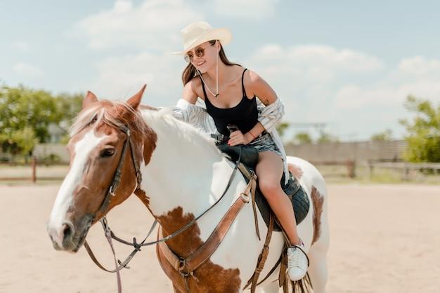 Vrouw die een paard in een platteland berijdt
