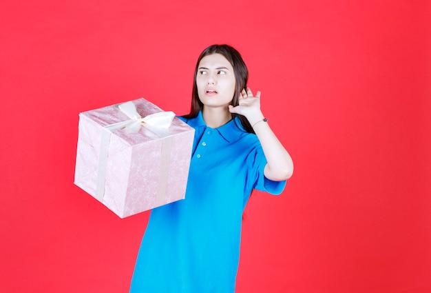 Vrouw die een paarse geschenkdoos vasthoudt en iemand belt om hem in ontvangst te nemen.