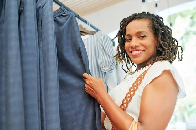 Vrouw die een pak in de winkel kiest