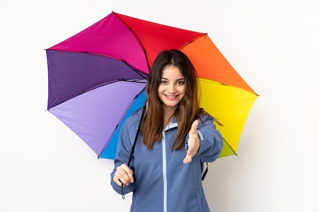 Vrouw die een paraplu houdt die op wit muurhandenschudden wordt geïsoleerd na veel