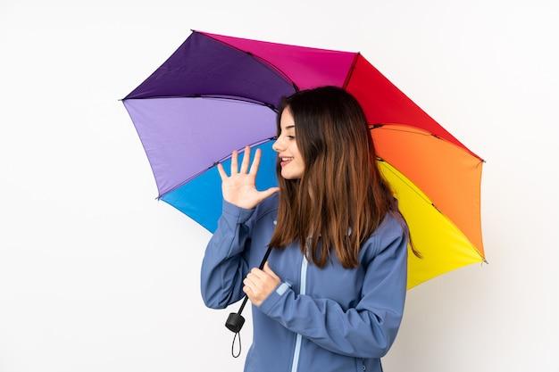 Vrouw die een paraplu houdt die op witte muur wordt geïsoleerd die met wijd open mond schreeuwt