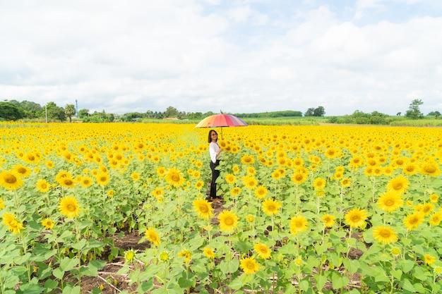 Vrouw die een paraplu op een zonnebloemgebied houdt.