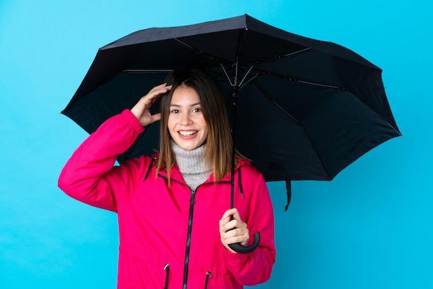 Vrouw die een paraplu over geïsoleerde blauwe muur houdt