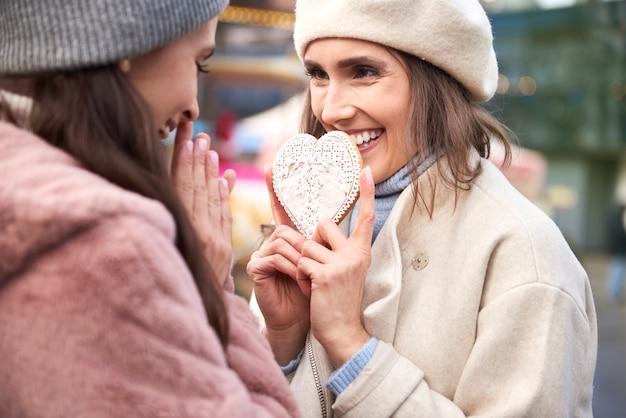 Vrouw die een peperkoek van de hartvorm houdt