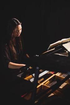 Vrouw die een piano in muziekstudio speelt