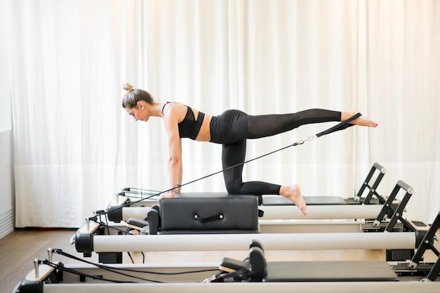 Vrouw die een pilates diagonale stabilisatie uitvoert
