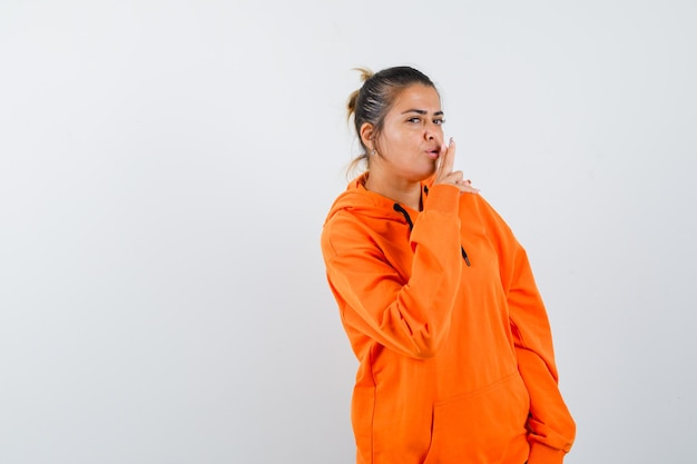 Vrouw die een pistoolgebaar in een oranje hoodie toont en er zelfverzekerd uitziet