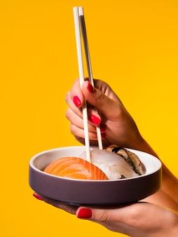 Vrouw die een plaat met sushi op een gele achtergrond houdt
