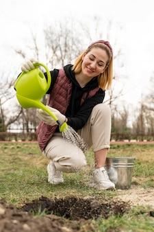 Vrouw die een plant water geeft die ze heeft geplant