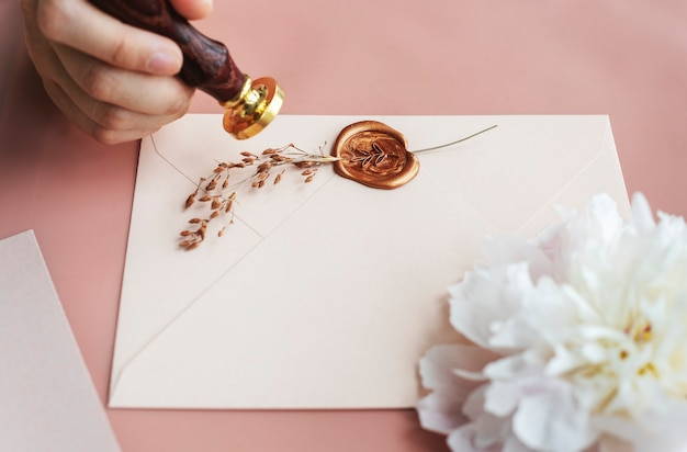 Vrouw die een postzegel op een envelopmodel zet Premium Foto