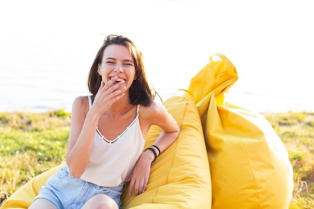 Vrouw die een prettijd op gele zitzakken heeft