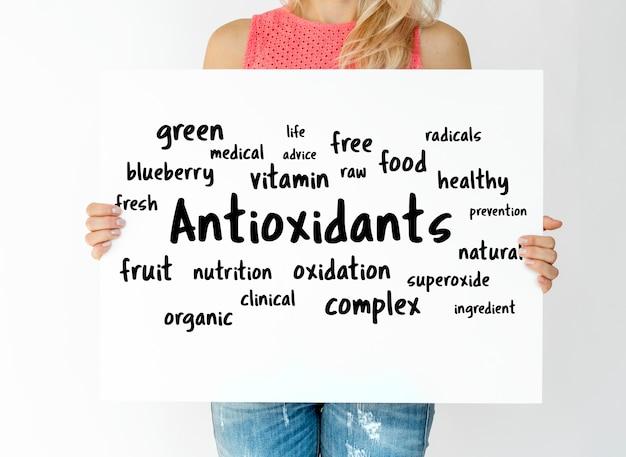 Vrouw die een raad met antioxidantenconcept houdt