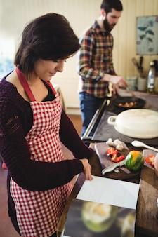 Vrouw die een receptenboek in keuken leest