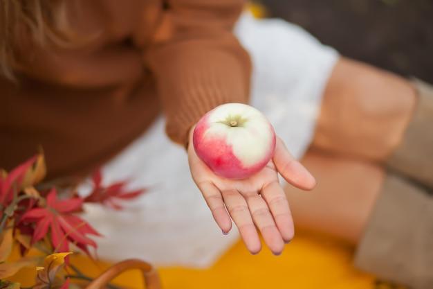 Vrouw die een rijpe appel op een de herfstpicknick houdt