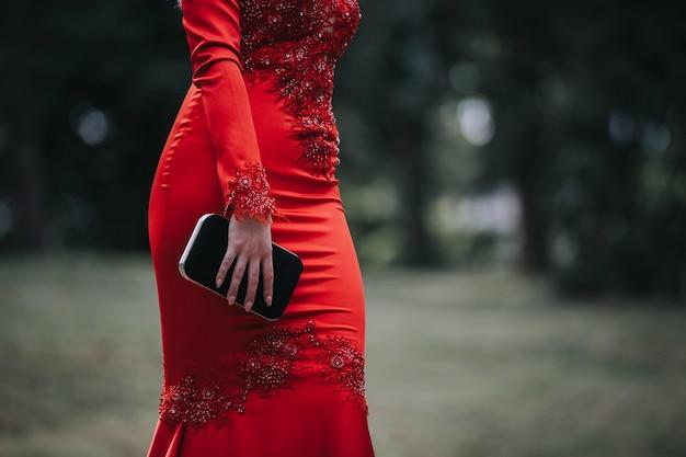 Vrouw die een rode sexy strakke jurk draagt en een portemonnee vasthoudt