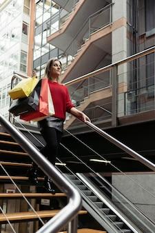Vrouw die een rode trui draagt die de trap van een winkelcentrum afloopt met boodschappentassen