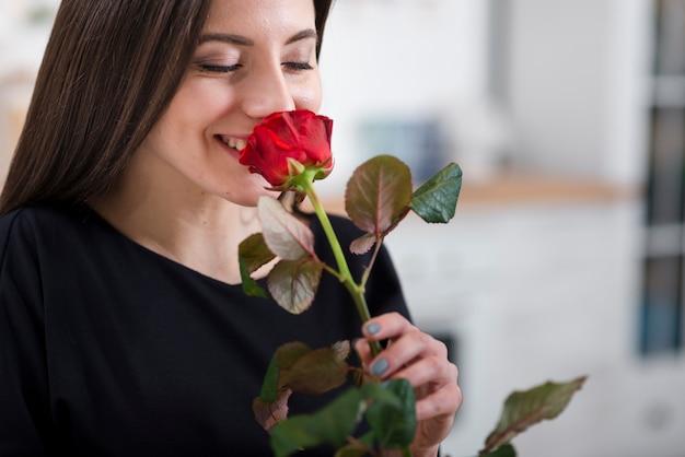 Vrouw die een roos van haar man ruikt