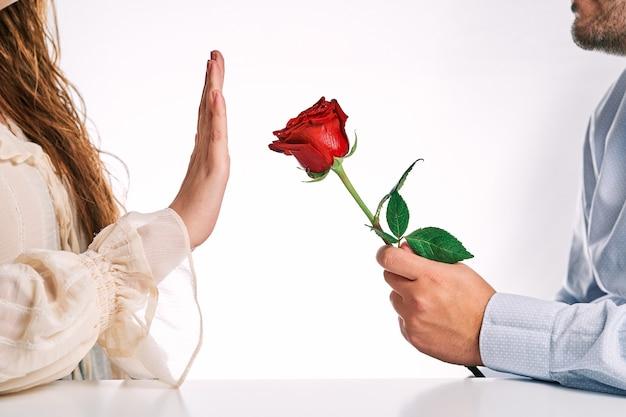 Vrouw die een roos van haar partner afwijst. concept van uiteenvallen, afwijzing en gebrek aan liefde.