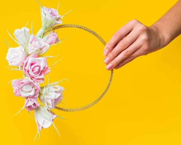 Vrouw die een rozenframe op gele achtergrond houdt