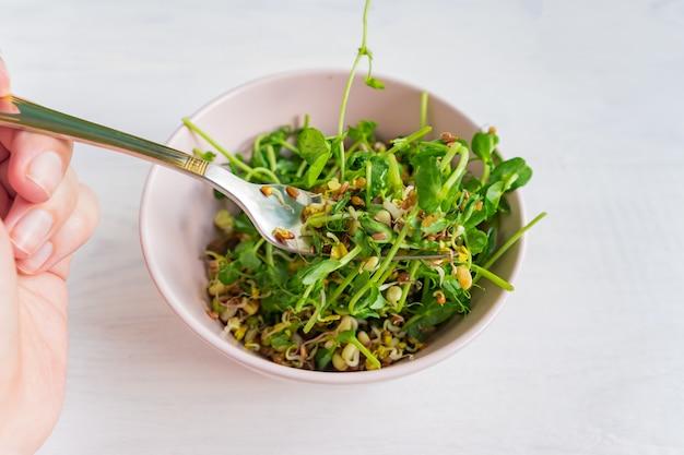 Vrouw die een salade eet die van erwten microgroene spruiten wordt gemaakt en gekiemde bonen. veganistisch gezond eten.