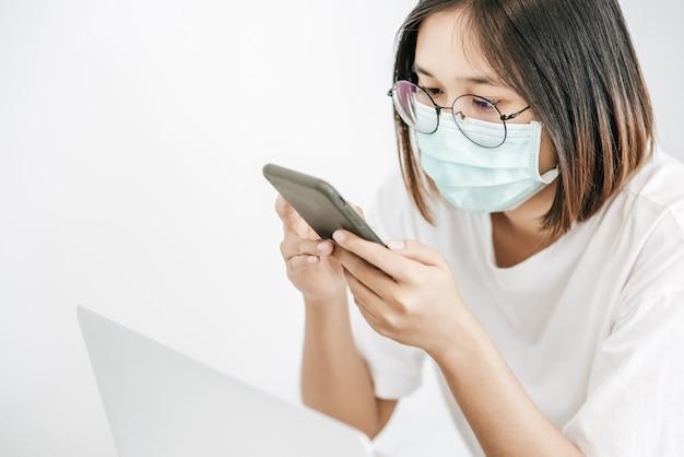 Vrouw die een sanitair masker draagt, een smartphone speelt en laptop heeft.