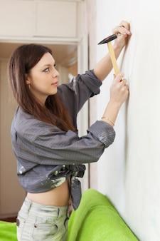 Vrouw die een schroef in de muur rijdt