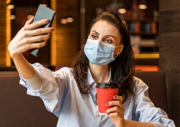 Vrouw die een selfie in een restaurant neemt terwijl ze een gezichtsmasker draagt