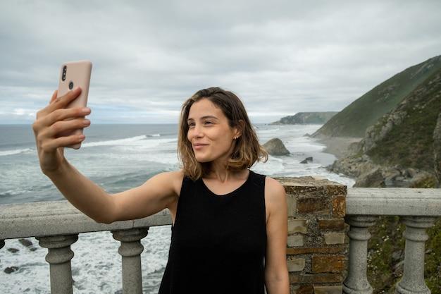 Vrouw die een selfie maakt met een bergachtige kust in noord-spanje