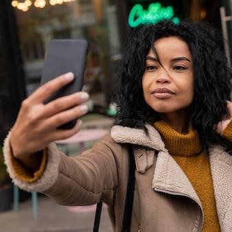 Vrouw die een selfie met haar smartphone buiten neemt